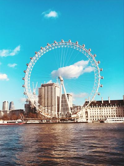 Millennium wheel by river in city against blue sky