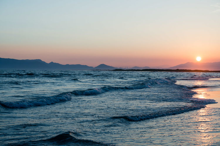 Aquatic Sport Beach Beauty In Nature Idyllic Land Motion Nature No People Orange Color Outdoors Scenics - Nature Sea Sky Sport Sun Sunset Tranquil Scene Tranquility Water Waterfront Wave