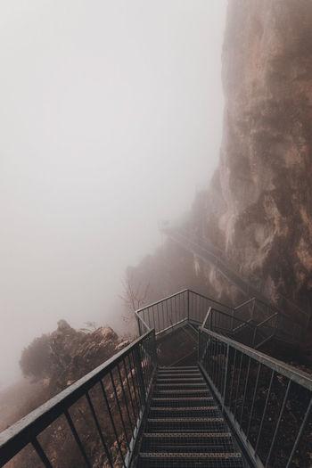 Staircase leading towards mountain against sky