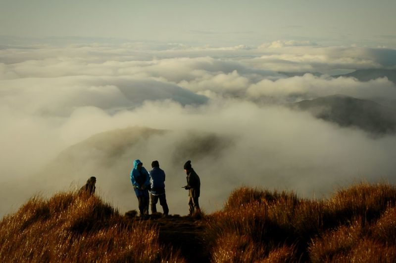 Hikers standing on mountain by cloudscape against sky