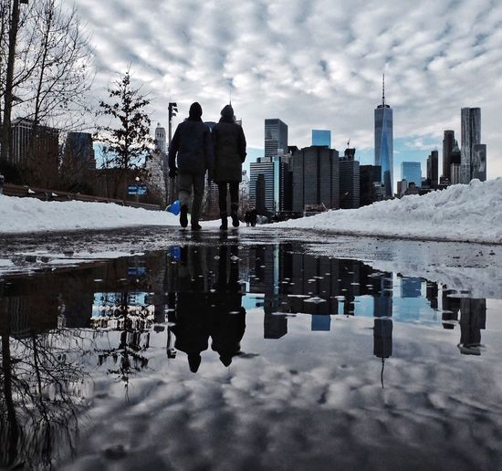 Rear view of people walking in puddle during winter
