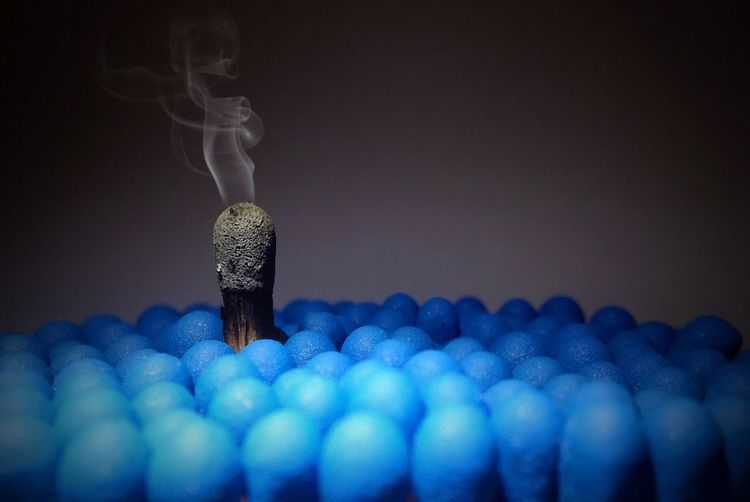Close-up of matchsticks and smoke against gray background