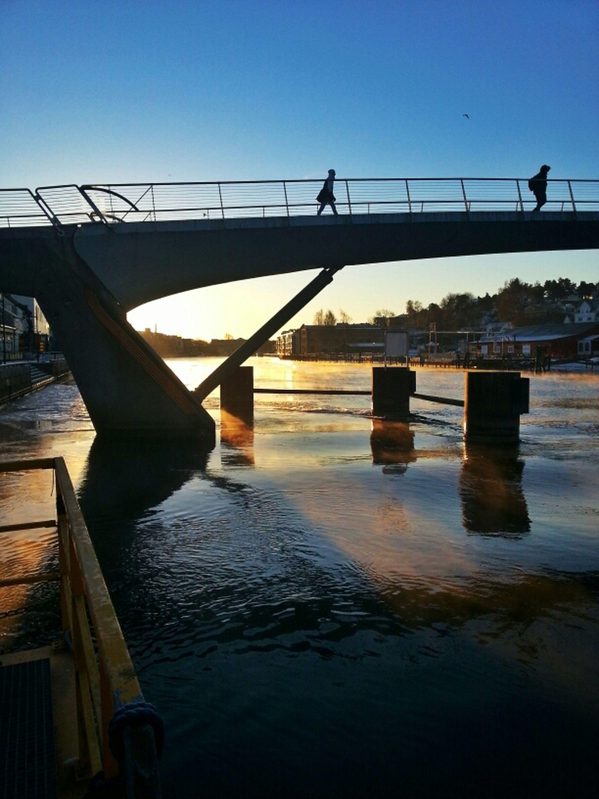 water, clear sky, built structure, transportation, men, bridge - man made structure, sea, architecture, pier, railing, lifestyles, river, nautical vessel, connection, sunlight, sky, standing, copy space