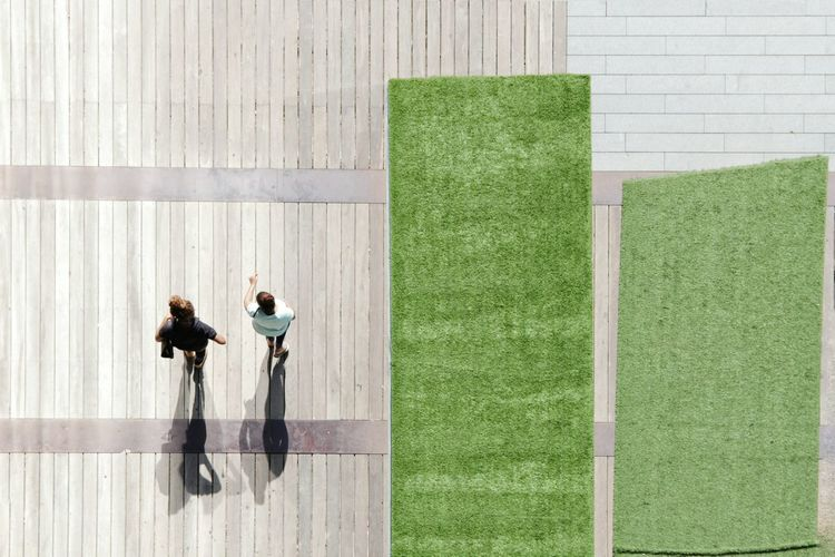 High Angle View Of People Walking On Wooden Floor By Green Carpets