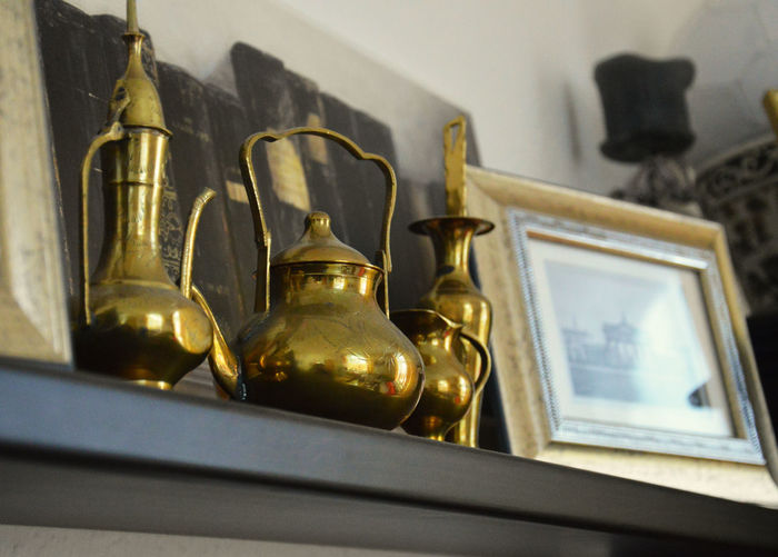 Low angle view of antique bronze utensils on shelf