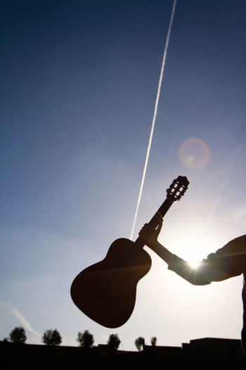 Cropped silhouette hand holding guitar against blue sky during sunny day