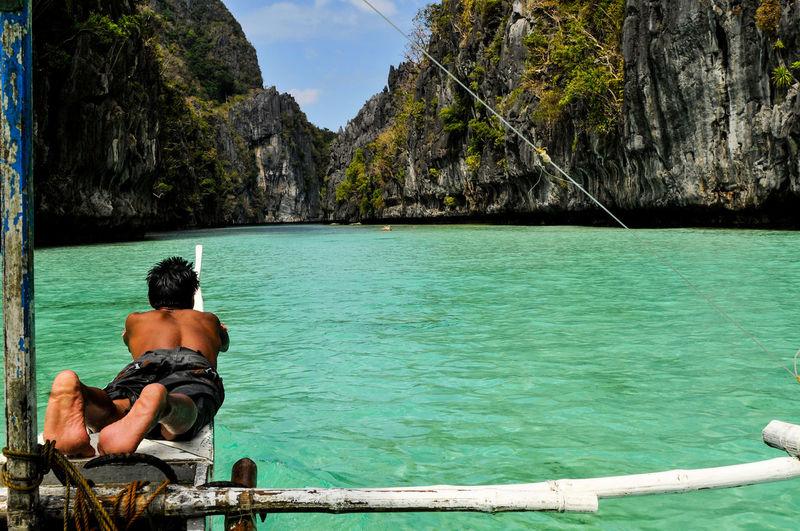 Rear view of shirtless man sitting in sea