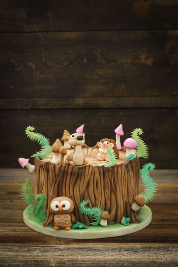 Enchanted forest woodland themed fondant cake with a hedgehog, deer, owl, tree trunk, ferns, mushrooms and leaves on wooden background with copyspace Birthday Cake Fondant Cake Tree Tree Trunk WoodLand Animal Cake Celebration Character Fern Figurine  Fondant  Food Food And Drink Forest Guitar Kid Mushroom Owl Still Life Sugar Arts Sweet Food Theme
