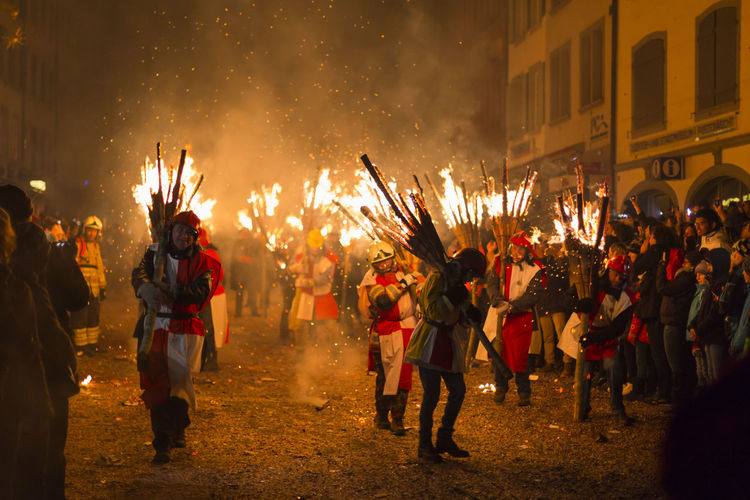 Chienbaese festival. Switzerland, Liestal, Rathausstrasse 25, 18th of February 2018. Festival participants carrying burning broom shaped wooden logs on their shoulders through the old town. Burning Flame Hot Old Town Tourist Attraction  Tradition Arts Culture And Entertainment Burning Burning Wood Candid Chienbaese Chienbäse Culture Danger Dangerous Editorial  Festival Fire Heat - Temperature Liestal Night Parade Real People Swiss Switzerland