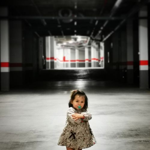 Portrait of cute girl standing in corridor