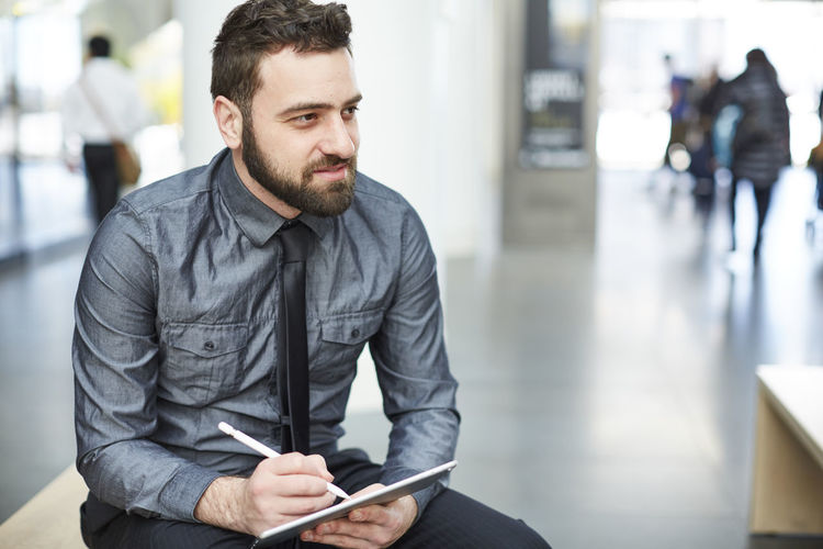 Businessman writing notes in diary while sitting at office