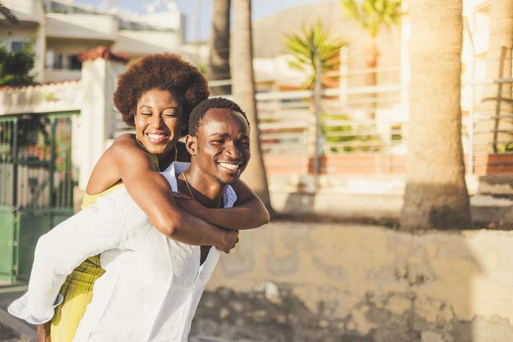 Boyfriend piggybacking girlfriend in city during sunny day