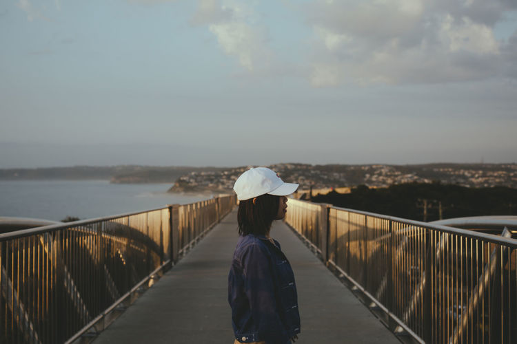 Side view of woman standing on footbridge against sky