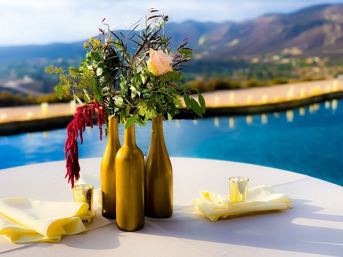 Close-up of yellow flower on table by swimming pool