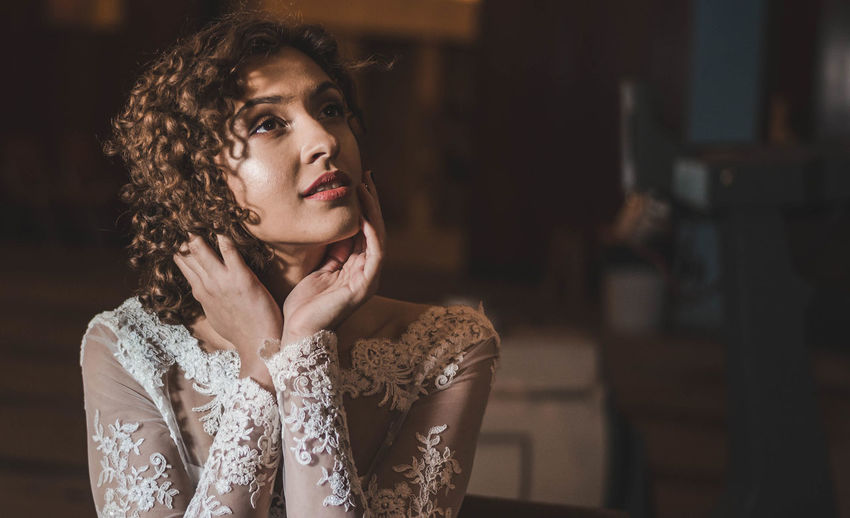 Thoughtful woman in wedding dress sitting with head in hands at home
