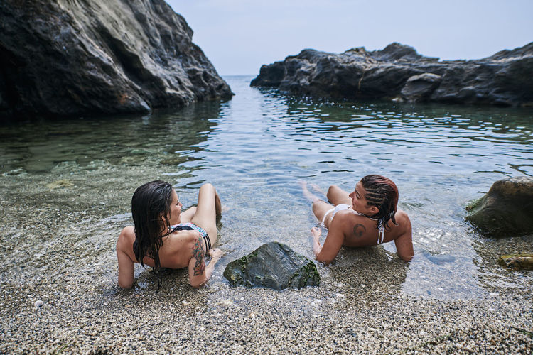 Two girls lying on the seashore sunbathing. holiday concept and lifestyle.