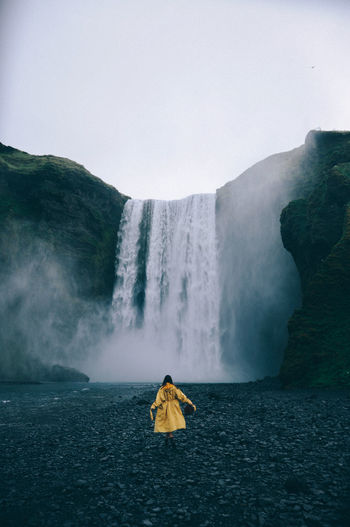 Rear view of  woman looking at waterfall against sky