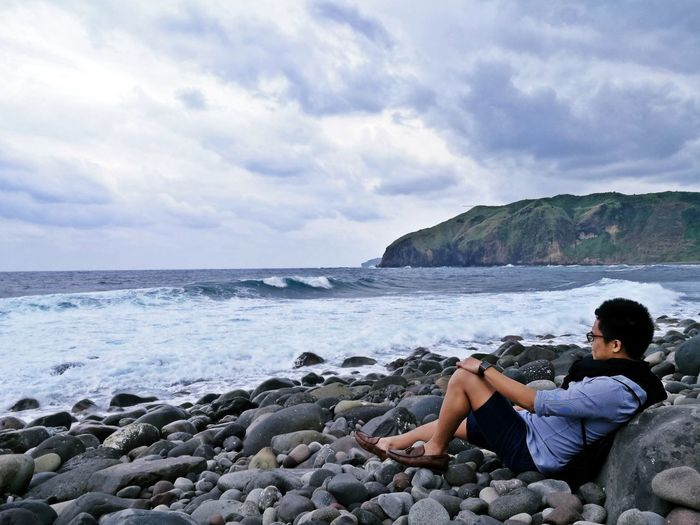 Man sitting on pebble stones at beach against sky