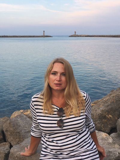 Water Sea One Person Blond Hair Rock - Object Real People Casual Clothing Sky Day Outdoors Sitting Young Women Looking At Camera Young Adult Horizon Over Water Women Standing Portrait