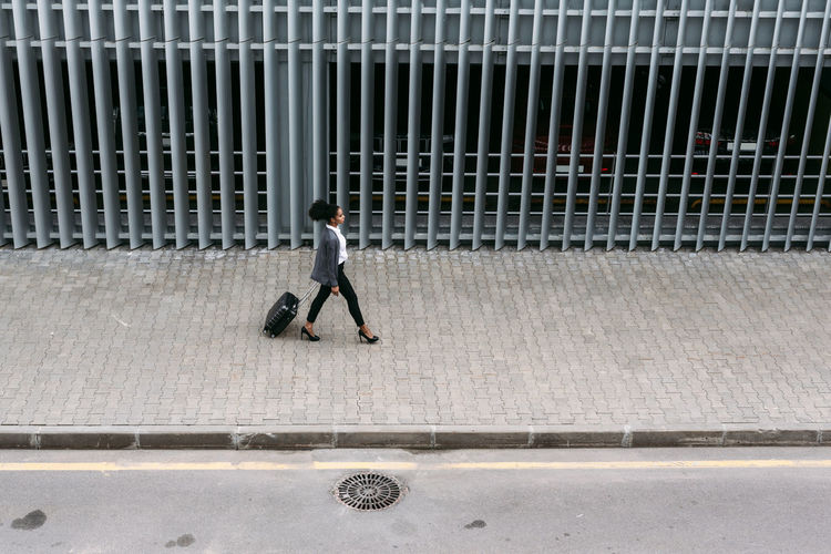 High angle view of woman with luggage walking on footpath in city