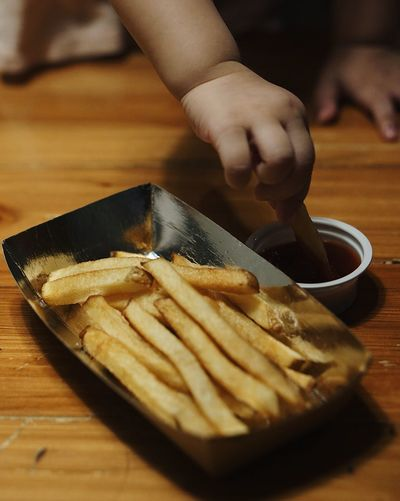 Cropped hand of child having french fries on table