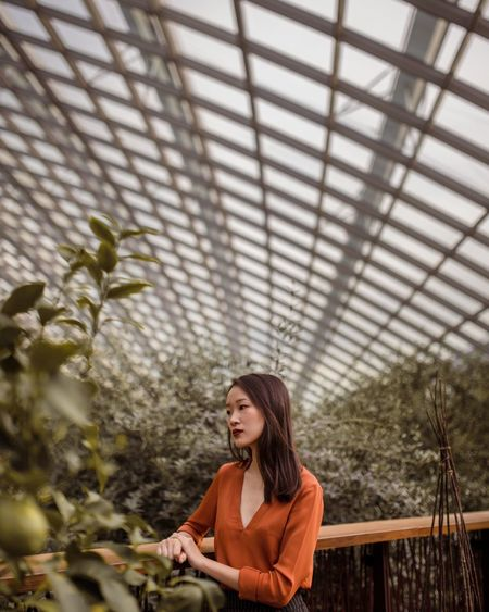 Portrait Of Young Woman Standing In Greenhouse