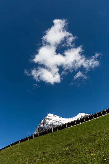 Tilt Image Of Hill And Snowcapped Mountain Against Sky
