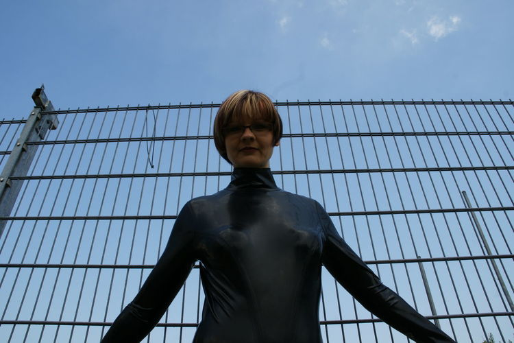 Low angle view of woman standing against fence