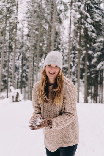 Portrait of a smiling young woman in snow