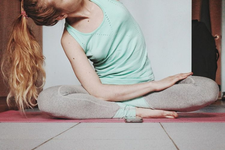 Low section of young woman doing yoga at home