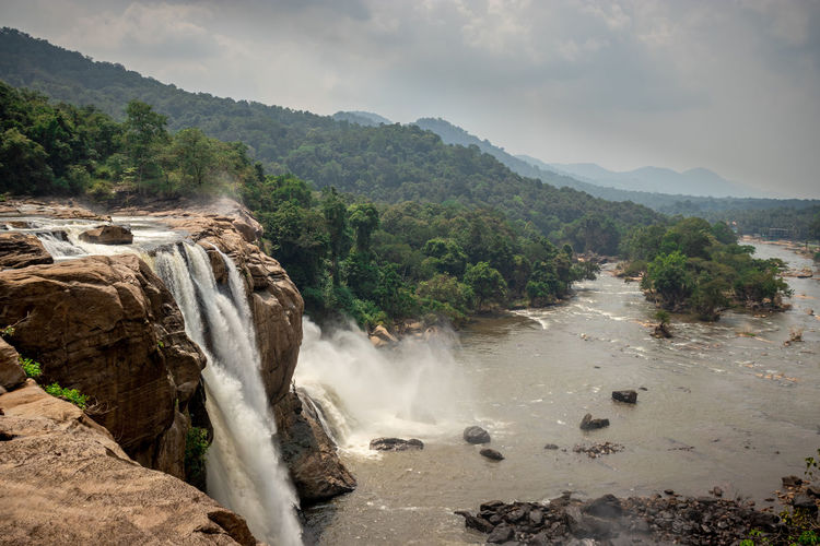 This is the athirapally waterfall kerala india from down angle view. It is falling from 80 mtrs high hill and it is the second largest waterfall in india. Athirapally Athirapallay Kerala Waterfall Mist Rock Rainny River Beautiful Adventure Cascade Scenic White Huge Flowing Storm Natural Stream Flow  Powerful Attraction Spray Tourist Forest Iceland Cochin Colorful Thrissur Chalakkudy Western Ghats Scenery ASIA Kochi Tourists Landmark Jungle Walking Stunning Sky Picturesque Green Spring Sholayar India Park Cloudy Chalakudy River Athirappalli Hiking