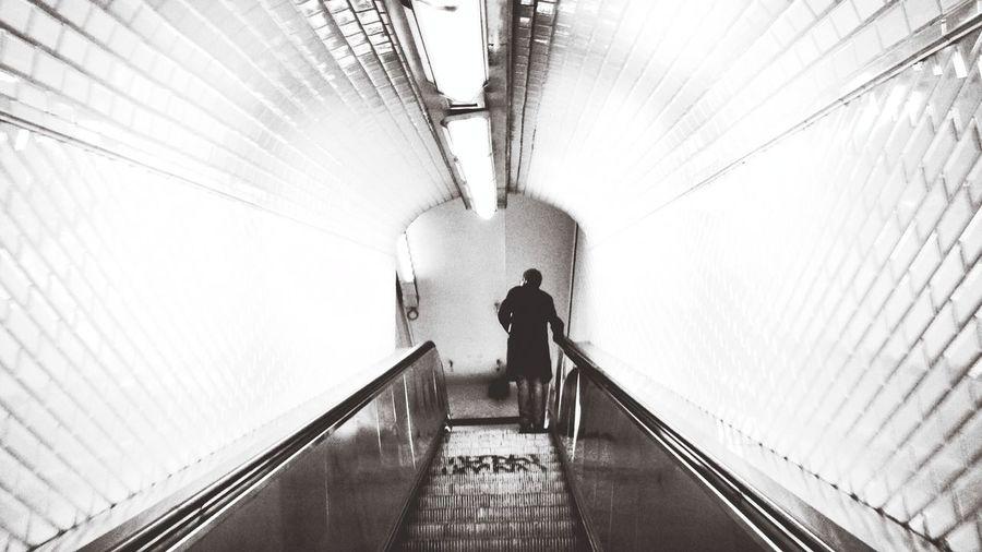 Rear view of woman walking on escalator in tunnel