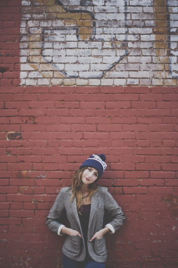 Portrait of beautiful woman standing against brick wall