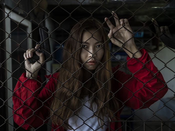 Portrait of a young woman looking through fence