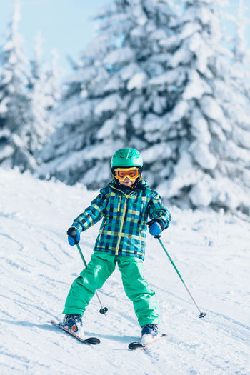 Skiing Ski Child Winter Vacations Snow Sport Childhood Boys Winter Sport Mountain Day Freedom Learning Cheerful Happiness Lifestyles Green White Outdoors Recreational Pursuit Activity Season  Hill Sunny Enjoyment Copy Space Motion Sliding Moving Down Elementary Age Physical Activity Ski Slope Sports Helmet Warm Clothing Stunt Color Image Fun Skill  Courage Caucasian Ethnicity Healthy Lifestyle Smiling Children Only Photography Ski-wear One Person Cold Temperature