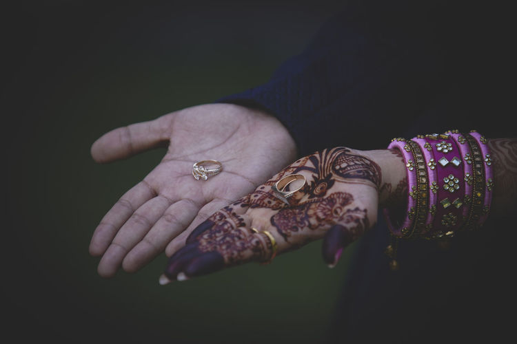 Close-up of bride and groom holding wedding rings