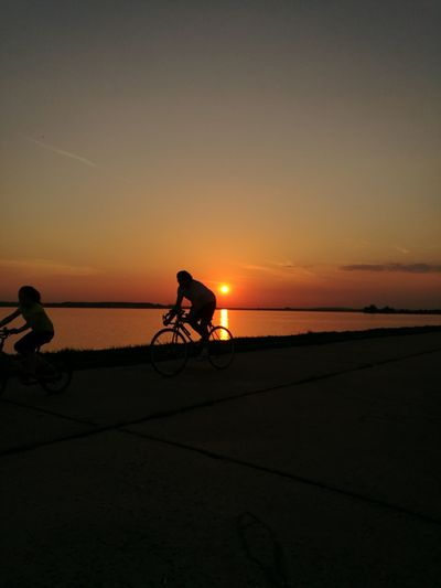 Silhouette people riding bicycle on shore against sky during sunset