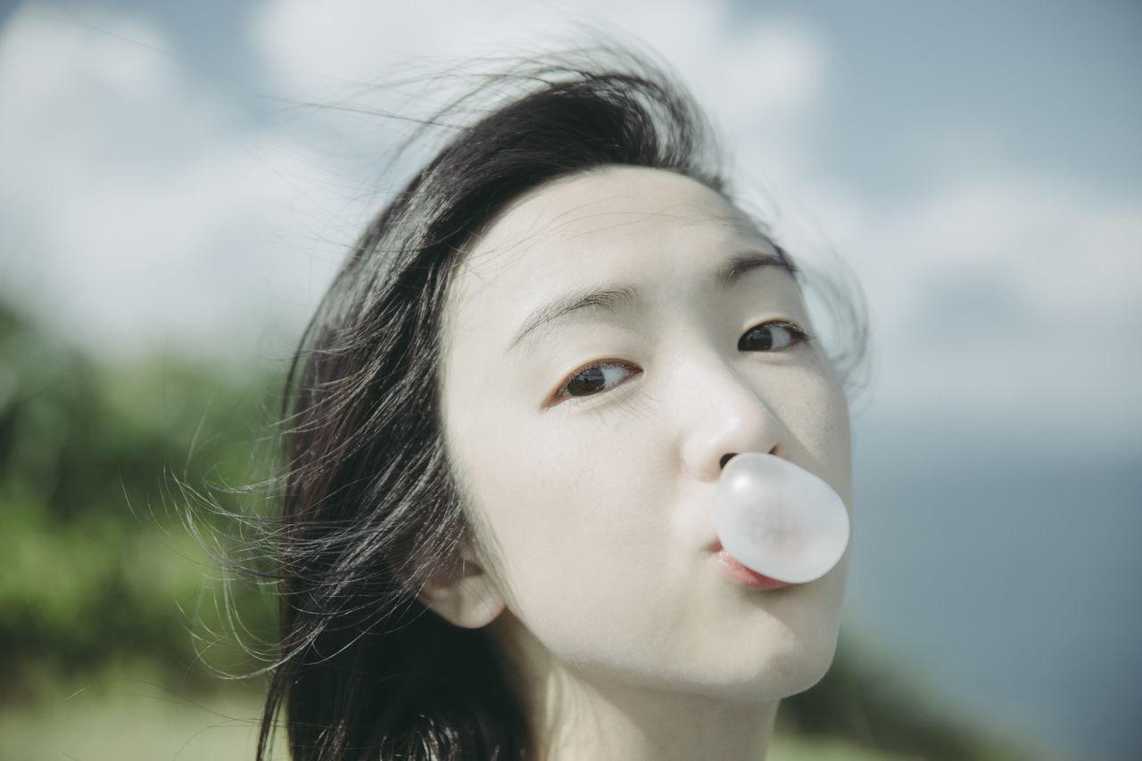 Close-up portrait of young woman blowing bubble gum