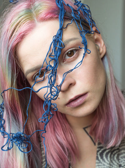 Close-up portrait of woman with threads on face