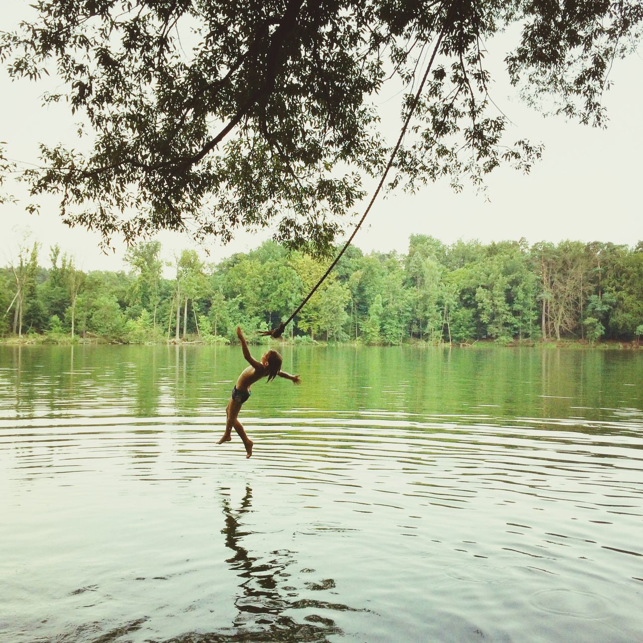 tree, rope swing, lake, one person, full length