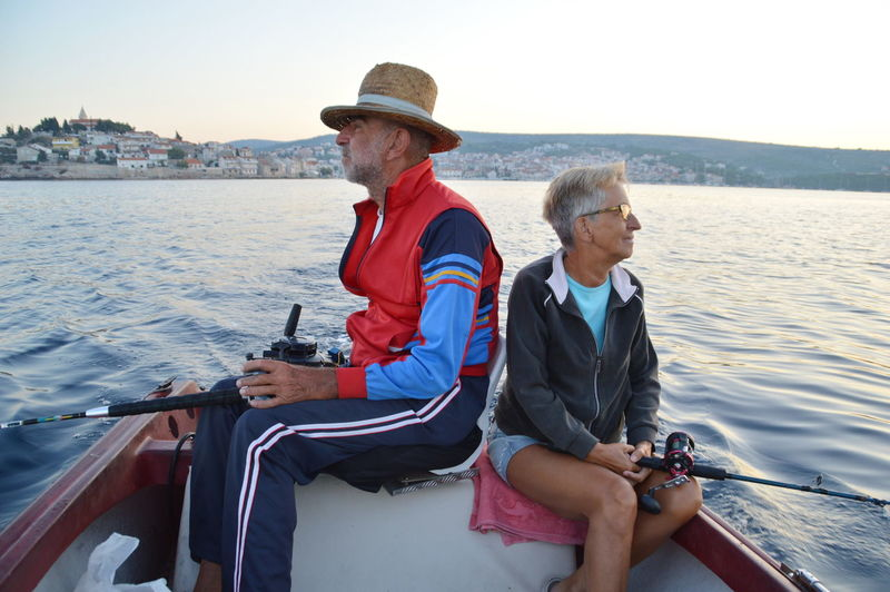 Senior man and woman sitting on boat in river against sky