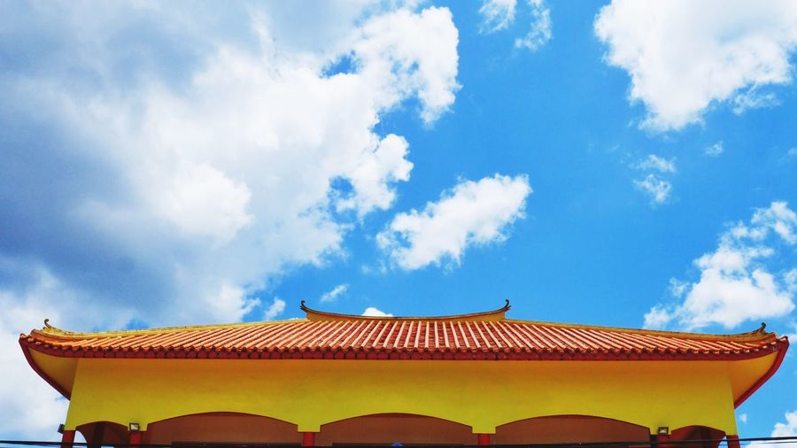 Low angle view of traditional building against cloudy sky