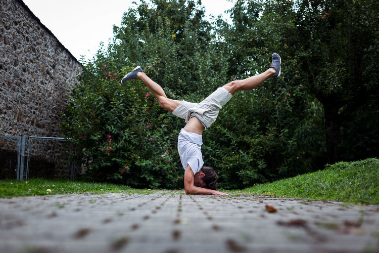 Young man exercising on footpath