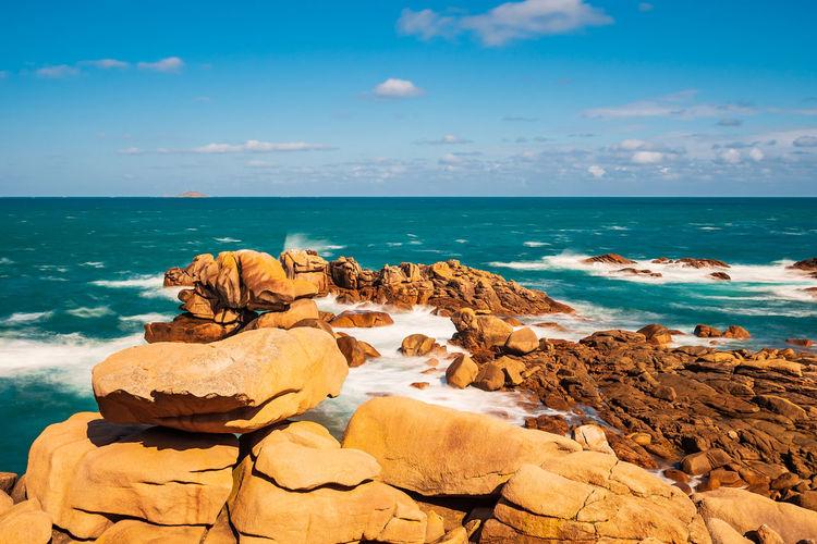 Rocks on beach against sky