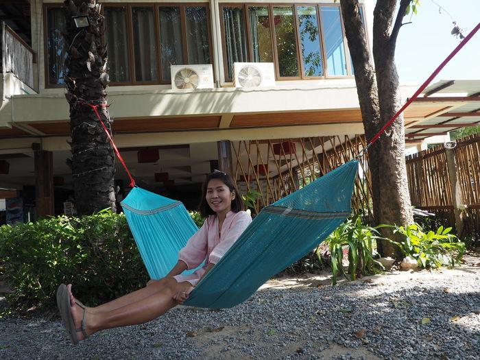 Portrait of woman sitting on hammock against plants