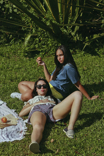 Friends Resting On Grassy Field At Park During Sunny Day