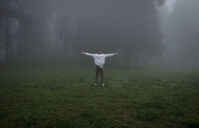 Full length of man standing on field in foggy weather