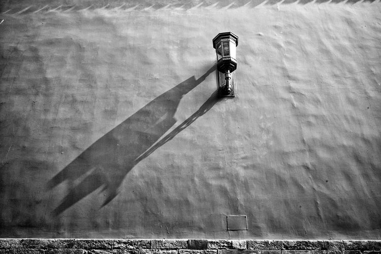 Low angle view of gas light with shadow on wall