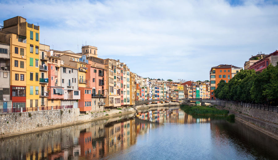 Canal amidst city against sky