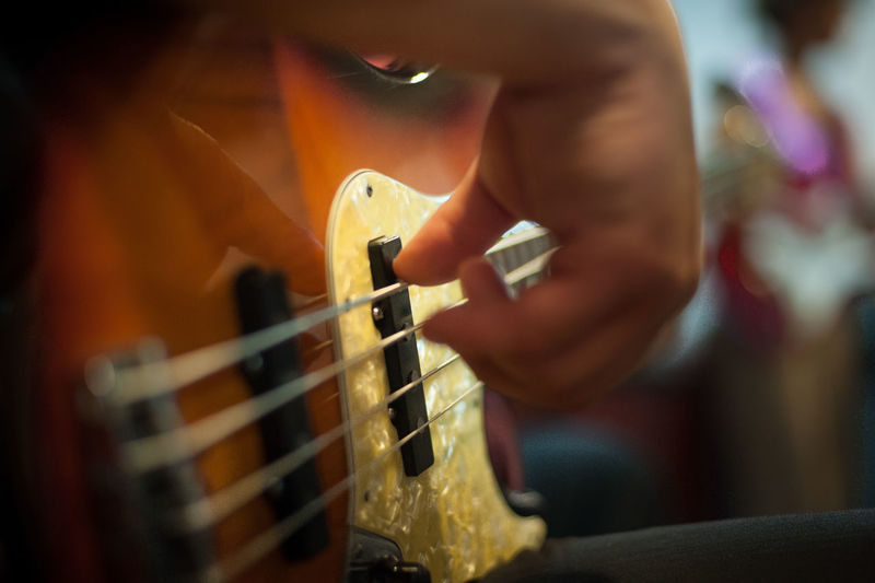 Midsection Of Person Playing Bass Guitar